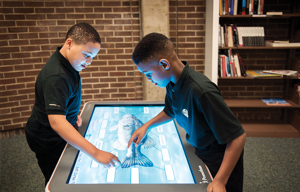 Fifth-grade students at Imani Christian Academy use a Promethean ActivTable for an interactive science lesson, part of their comprehensive science, technology, engineering, and math curriculum.